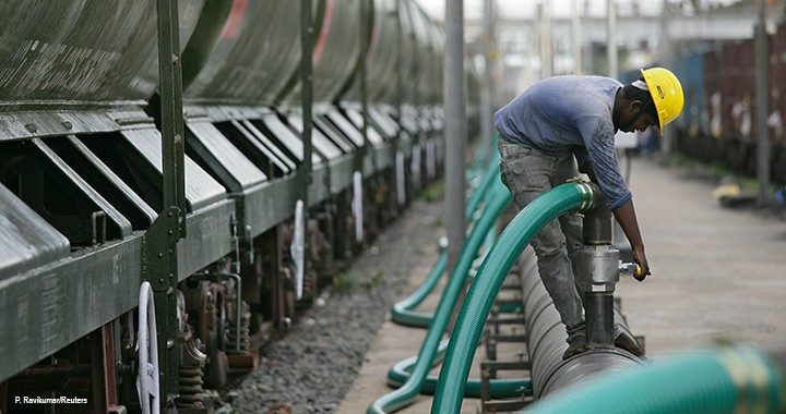 A technician checks a valve before water is pumped into a tanker train. The water will be supplied to the drought-hit city of Chennai in India.
