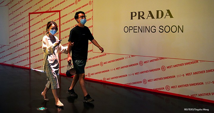 People wearing face masks following the COVID-19 outbreak walk past a store of Italian luxury brand Prada to open soon inside a shopping mall in Beijing, 19 September 2020.