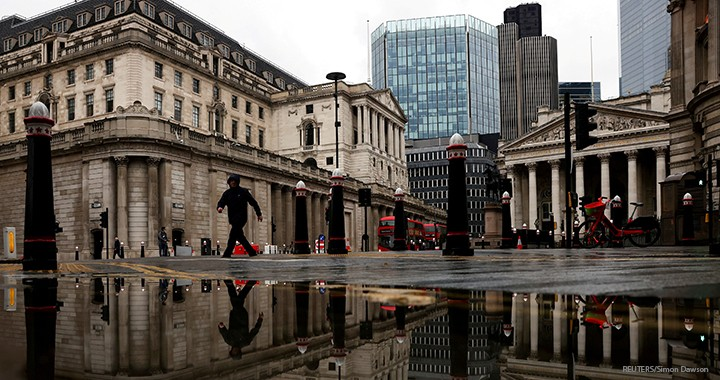 The Bank of England and Royal Exchange are reflected in a puddle as a pedestrian walks past, amid the coronavirus outbreak in London.
