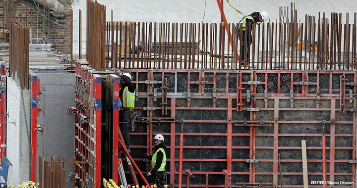 Construction workers are seen working at a site in London.