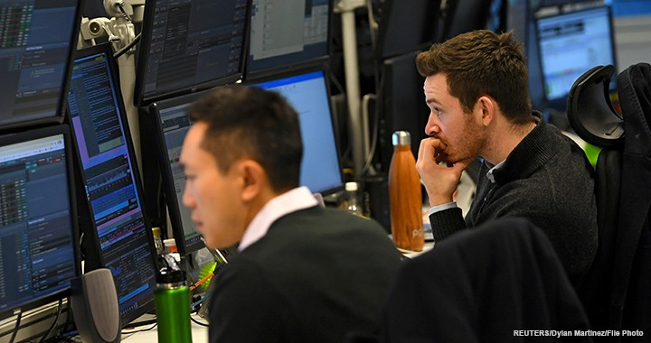 Dealers work at their desks whilst screens show market data following a vote on Prime Minister Theresa May's Brexit 'plan B' at CMC Markets in London, 30 January 2019.