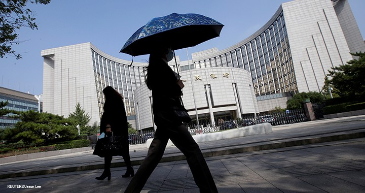 People walk past the headquarters of the PBOC, the central bank, in Beijing.