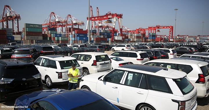 A worker inspects imported cars at a port in Qingdao, Shandong province, China.