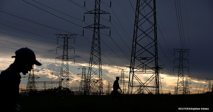 Men walk past electricity pylons as they return from work in Orlando, Soweto township, South Africa, on 18 March 2019.