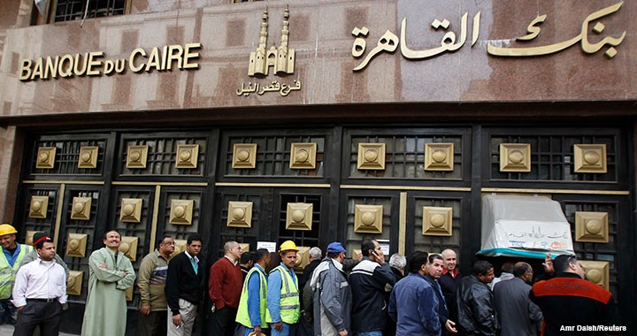 People stand in line to make withdrawals outside Cairo Bank in downtown Cairo on 6 February 2011, the first day for the country's banks to open after a weeklong closure due to political protests.