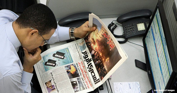 An Egyptian trader reads a local newspaper, which features coverage of clashes between protesters and security forces, at the Egyptian stock exchange in Cairo on 20 November 2011.