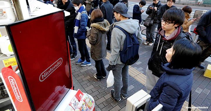 People queue up to purchase the Nintendo Switch game console outside an electronics store in Tokyo in March 2017.