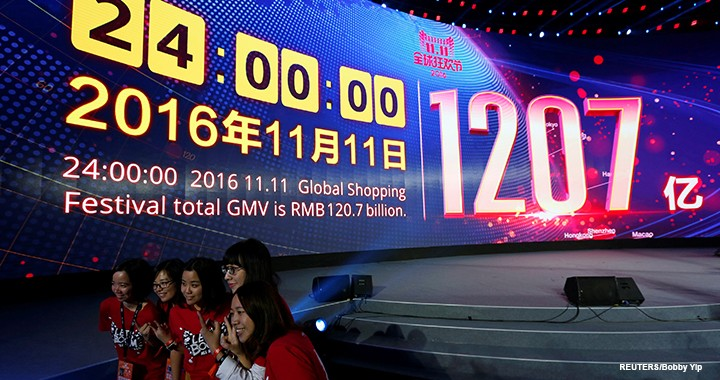 Attendants celebrate in front of  a screen displaying the total value of goods sold during Alibaba Group's 11.11 Singles' Day global shopping festival in Shenzhen, China.