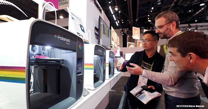 CES attendees check out a display of Polaroid PlaySmart 3D printers.